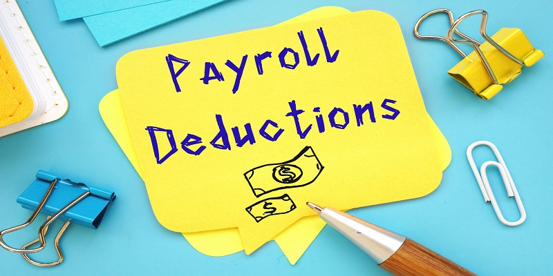 Yellow sticky note with text displaying Payroll Deductions and a couple of binder clips scattered